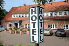 Leuchtreklame Hotel am Straßenrand - lang gestrecktes Gebäude mit mehrteiliger Fenstergaube.