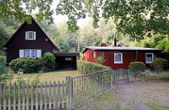 Holzhaus mit Spitzdach  und Fensterläden mit Carport  und Holzzaun / flaches, schlichtes Holzhaus.