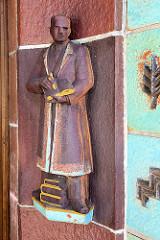 Terrakotta Figur / Angestelltenfigur am Eingangsbauwerk der ehemaligen Margarinefabrik Voss in Hamburg Barmbek/Nord.
