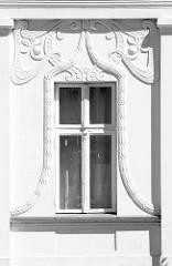 Fensterreliefs im Jugendstil, florale Bänder an der weißen Hausfassade; historische Architektur in Neustrelitz.