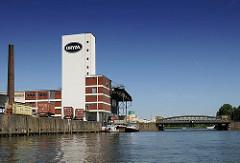 Reismühle auf der Peute von Hamburg-Veddel. Blick über den Peutekanal zur Kaianlage, an der die Fracht eines Binnenschiffs gelöscht wird.