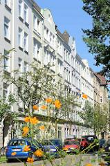 Wohnstraße  mit mehrstöckiger Gründerzeitarchitektur im Hamburger Stadtteil  Altona-Nord;  blühende Blumen am Straßenrand.
