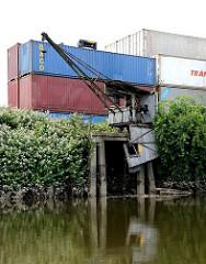 Containerlager mit leeren Containern am Ufer des Schmidtkanals - alter, verrotteter Hafenkran.