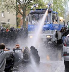 Eine Straßenblockade wird bei einer Demonstration in der Freien und Hansestadt Hamburg mit Hilfe eines Wasserwerfers aufgelöst. Mit Helm geschützte Fotografen fotografieren.