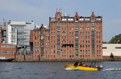 Ein gelbes Sportboot mit Aussenbordmotor fährt auf der Billwerder Bucht Richtung Sperrwerk. Am Ufer das historische Speichergebäude mit der roten Ziegelfassade.