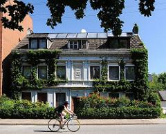Das Gründerzeit-Wohngebäude in der Wilhelmsburger Strasse Vogelhüttendeich ist dicht mit Efeu bewachsen. Die Fassade ist hellblau gestrichen.
