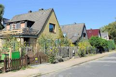 Einzelhäuser  mit Satteldach  und kleinem Vorgarten - unterschiedliche Fassaden Gestaltung; ruhige Seitenstraße in Hamburg Bramfeld.