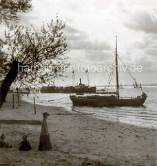 Altes Bild vom Elbufer in Hamburg Blankenese;  Kinder spielen am Sandstrand - ein Segelschiff liegt am Ufer vor Anker.
