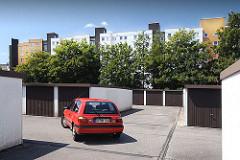 Garagenanlage in der Wohnsiedlung Kirchdorf Süd. Ein roter PKW verlässt seinen Stellplatz und wird zur Strasse gefahren.
