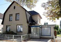 Wohnhaus mit  Mansarddach und gelber Klinkerfassade,  angeschlossenem ehemaligen Ladengeschäft für Milch  und Feinkost.