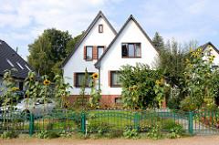 Doppeltes Wohnhaus / Doppelhaus  mit Spitzdach - blühende Sonnenblumen im Vorgarten.