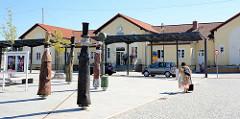 Empfangsgebäude vom Bahnhof Neustrelitz  / Vorplatz mit Holzskulpturen.