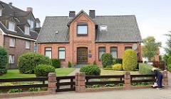 Einzelhaus in historischer Backsteinarchitektur mit Dachgiebel über dem Eingang; Ziegelpfeiler mit Holzzaun.