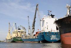 Mehrere Frachter liegen am Reiherstiegkai; in der Mitte die 100m lange und 20m breit OXL NOMAD.  Die bordeigenen Krane / Ladegeschirr machen das Schiff beim Laden und Löschen.