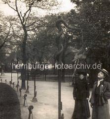 Historische Ansicht  vom Hamburger Zoologischen Garten iin Wallanlagen; zwei Frauen  in Kostümen mit Hut stehen vor einem Papagei.