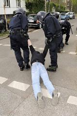 Ein Demonstrant wird von freundlichen Polizisten um Begleitung gebeten -  Demonstration in Hamburg Barmbek.