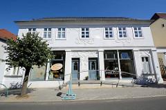 Doppelhaus im Baustil Art Nouveau, florale Reliefs an der weißen Hausfassade.