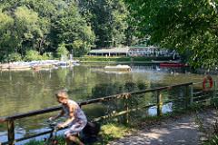 Bootsverleih am Mühlenteich / Alster in Hamburg Fuhlsbüttel - Gartenrestaurant, Café. Im Vordergrund eine Fahrradfahrerin auf dem Alsterwanderweg.