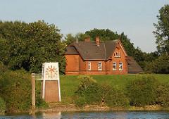 Eine Pegeluhr steht am Ufer der Norderelbe bei Kaltehofe, die Zeiger sind überklebt - die Anzeige funktioniert nicht mehr. Hinter dem Deich ragt eines der Verwaltungshäuser der ehem. Stadtwasserkunst.