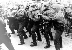 Polizisten in Kampfmontur zeigen Interesse an den Demonstranten, freundlich bereiten sie sich auf die nonverbale Kommunikation vor / Polizeieinsatz  Hamburg.