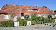 Siedlungsreihenhaus der 1930er Jahre in der Rotdornallee in Hamburg Bramfeld. Eingänge für drei Wohneinheiten und kleinem Vorgarten.