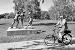 Skulptur Handballspielerinnen im Kulturpark Neubrandenburg - Bildhauerin Senta Baldamus. Schwarz Weiss Bild mit Radfahrer.