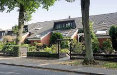 Reihenhäuser mit tief heruntergezogenen Dach - Fenstergauben mit Balkon; bunkerähnliche Architektur in Maschen.