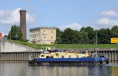 Ein Schubschiff fährt auf der Billwerder Bucht Richtung Sperrwerk zur Elbe. Im Hintergrund der Turm der Wasserkunst von den Wasserwerken Rothenburgsort.