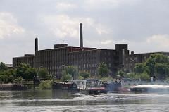 Eine Barkasse fährt im Peutehafen zu ihrem Liegeplatz - weitere Arbeitsboote und Binnenschiffe haben in dem Veddeler Hafenbecken fest gemacht.