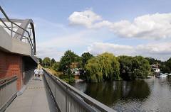 Eine Fussgängerbrücke führt neben der Eisenbahnbrücke über den Bullenhuser Kanal - zwei Fussgängerinnen überqueren die Brücke.  Am Ufer des Kanals wachsen auf dem Kleingartengelände Weiden.
