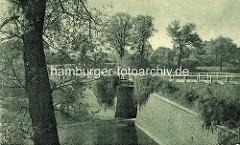 Altes Bild von der Alsterschleuse bei Wohldorf - Hansestadt Hamburg. Das Altsterbecken bei der Schleuse iist mit einer Ziegelmauer eingefasst, rechts ist ein Treppenabgang zu erkennen; oben verläuft die Landstraße, die mit einem Bretterzaun  einge