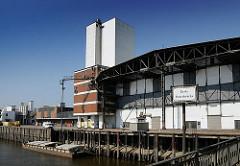 Die Ladung einer Schute wird gelöscht - über eine Sauganlage wird das Schüttgut in den Speicher transportiert. Eisendalben vor der Kaianlage dienen zum Festmachen der Schiffe.