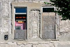 Mit Spanplatten teilweise vernagelte Fenster, Neu Neu Neu! Musterausstellung zwischen abgebröckeltem Putz und mit Lehm verputzten Strohmatten gefüllten Fachwerk.