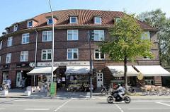 Halbrundes Backsteingebäude, Architektur der 1930er Jahre; Kaffee und kleine Bäckerei mit Sitzplätzen in der Sonne.