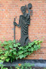 Metallrelief des heiligen Christophorus  mit Jesus auf der Schulter - Hausfassade der Christophorus Kirche in Hamburg Hummelsbüttel.