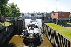 Ein Binnenschiff hat seine Fracht im Hamburger Hafen gelöscht und fährt ohne Ladung durch das geöffnete Schleusentor der Reiherstiegschleuse.