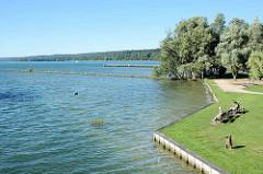 Ufer vom Tollensesee in Neubrandenburg - Bänke mit Parkbesuchern, Kulturpark Neubrandenburg.