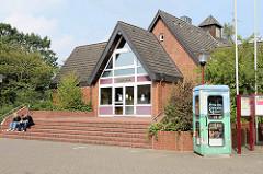 Moderne Architektur  der 1970er Jahre / Dorfhaus, Rathaus von Maschen - auf dem Dach die alte Uhr Schule. Rechts eine alte Telefonzelle, die als öffentlicher Bücherschrank genutzt wird.