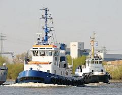 Die beiden Schlepper FAIRPLAY VI und HANS fahren auf dem Reiherstieg, um ein dort abfahrbereites Frachtschiff   zu schleppen.