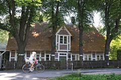 Strohdachhaus in Hamburg-Georgswerder; die Fachwerkbalken des historischen Gebäudes sind weiss gestrichen.