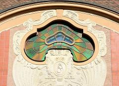 Oberlicht mit farbigem Glas und weichen Rundungen, Monogramm im Maskeron - florale Reliefelemente im Stil von Art Nouveau - Wohnhaus in Neustrelitz.