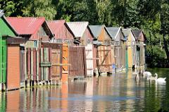 Bootshäuser mit farbigen Holztüren - Bootsliegeplätze am Oberbach in Neubrandenburg.