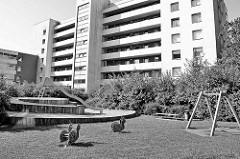 Hochhaussiedlung in Hamburg Hummelsbütte - einsame Wackelschnecken auf dem Kinderspielplatz mit Rutsche und Schaukel.