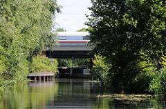 Blick vom Ernst-August-Kanal zur Mündung der Wilhelmsburger Dove-Elbe; ein Zug fährt über die Eisenbahnbrücke.