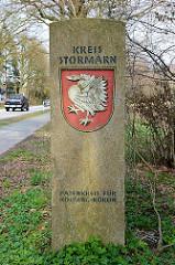 Grenzstein - Grenze zum Kreis Stormarn in Schleswig-Holstein; eingraviertes Wappen - silberner  Schwan in Kampfstellung mit goldener Krone um den Hals.