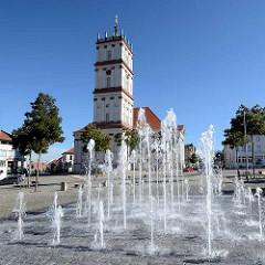 Springbrunnen am Marktplatz von Neustrelitz - Blick auf die Stadtkirche, die ursprünglich 1778 nach Plänen des Hofarztes Johann Christian Wilhelm Verpoorten errichtet wurde.
