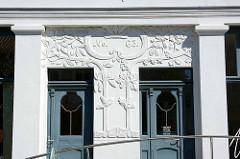 Eingang Doppelhaus im Jugendstil, florale Reliefs an der weißen Hausfassade; historische Architektur in Neustrelitz.