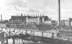 Historisches Foto aus Hamburg Wilhelmsburg ca. 1920 - am Ufer des Veringkanals sind Baumstämme gestapelt; an den Kaianlagen liegen Schuten.