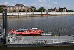 Eine rote Barkasse der Maritimen Circle-Line macht gerade am Anleger Ballinstadt fest gemacht. Das Schiff ist mit Touristen voll besetzt.
