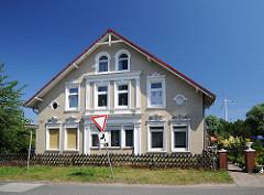 Gründerzeit-Gebäude am Niedergeorgswerder Deich - die Fassade des Bauernhauses ist mit gelbem Klinker verkleidet und die Fenster sind mit weisses Stuckdekor..